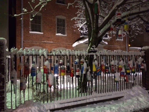 Lobster buoys painted with the flags of the homelands of Maine's immigrant population decorate the fence in front of the former home of Henry Wadsworth Longfellow in Portland, Maine; Aquarius the sign of groups. - AMANDA PAINTER