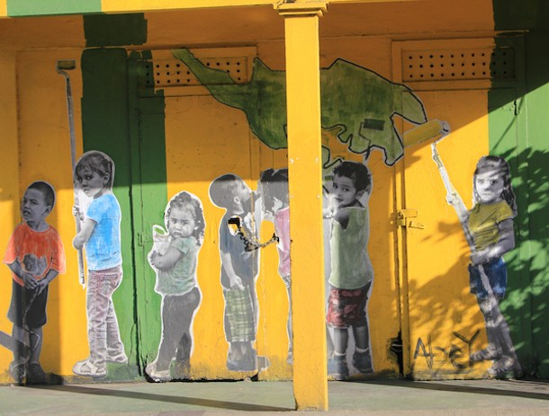 Wheat-paste mural of children painting a building in downtown Dewy, Isla de Culebra, Puerto Rico. - AMANDA PAINTER