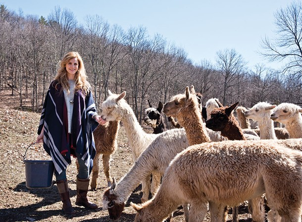 "Alicia Adams, in an alpaca wool shawl, feeding her alpaca herd. Her ""guilt-free fur"" products are made from the animals' sheared winter coats - DEBORAH DEGRAFFENREID"