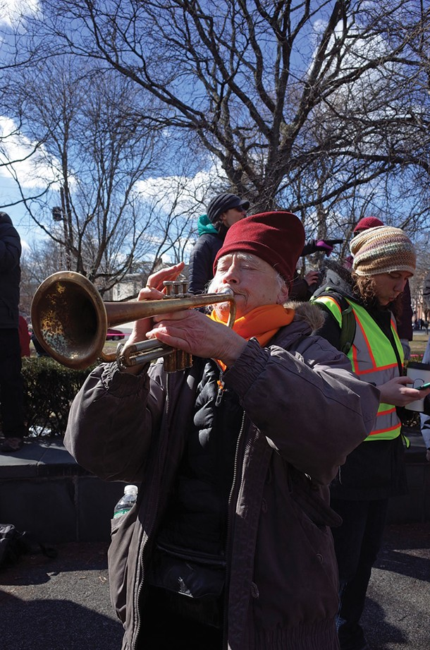 Amy Trompetter sounds a musical protest at the People's March for Education Justice. - FIONN REILLY