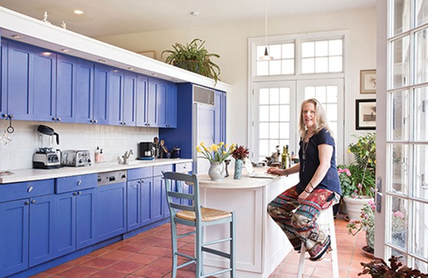 """Susan Coleman in her kitchen. Once the home's former den, she added a kitchen island, ceramic tiles, and French doors leading to a bluestone patio—all of it looking out over the property's lake and woods. """"I recently heard a historian explain that men finally stopped dueling when women started laughing when they dueled. Women have a lot of power. Empowering women, especially, leads to more peace. - DEBORAH DEGRAFFENREID"""