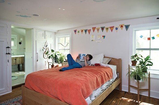 James in his bedroom with en suite bath. The wide-plank wood floors are original to the house; during the remodel, they were sanded and re-stained. - DEBORAH DEGRAFFENREID