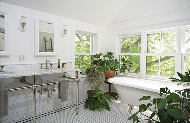 Upstairs, captured space from an underutilized porch was reborn as a large family bathroom with hexagonal subway tiles and west facing windows. On sunny afternoons the clawfoot tub is bathed in light. - DEBORAH DEGRAFFENREID