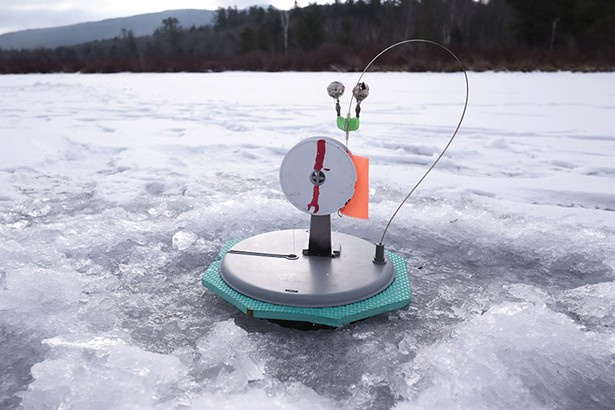 One of Sergey's tip-ups, the device that sits over a hole in the ice and alerts anglers to a bite. When a fish takes the bait, the orange flag pops up. The angler then pulls in the line by hand. In his first hour on the lake, Sergey had caught four fish. - PHOTO BY ROY GUMPEL