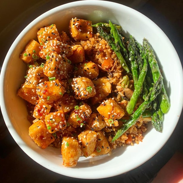 Vegan crispy tofu special with vegetable fried rice and chili sauce.