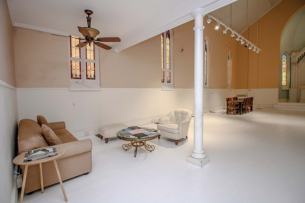 """A seating area under the choir loft turned bedroom enjoys afternoon light through the stained glass windows. """"The quality of light in this region is incredibly special. One of the reasons so many artists have migrated to Hudson over the past 200 years is for the light,"""" Bokaer says. """"On winter afternoons around four that light phases through these windows—it's breathtaking."""" - PHOTO BY SETH DAVIS"""