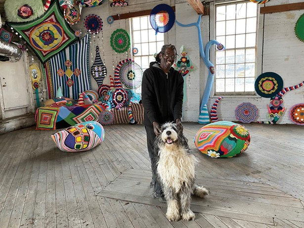 Gallery visitor Josh Shaw with ArtPort dog-in-residence Rubi(n) in front of an installation by Jelia Gueramian inside the Cornell Steamboat Building in Kingston - PHOTO BY STEFAN SAFFER