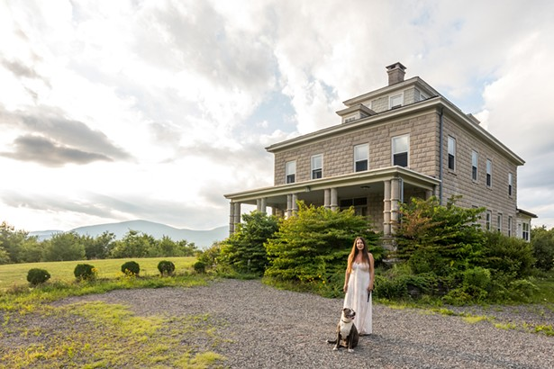 Diane Raimondo and her dog Layla in front of her hundred-year old stone house. Overlooking the Ashokan Reservoir, the historic home was built by the Ashokan's chief engineer, J. Waldo Smith. - PHOTO BY WINONA BARTON-BALLENTINE