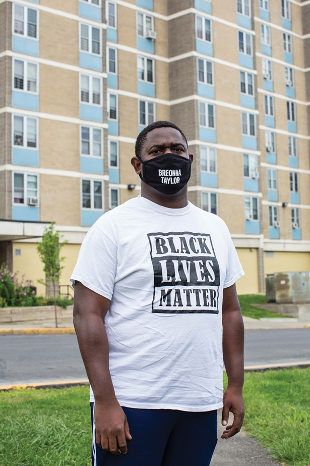 Quintin Cross in front of Bliss Towers, one of the only afforable housing developments in Hudson. - PHOTO BY ANGELINA DREEM