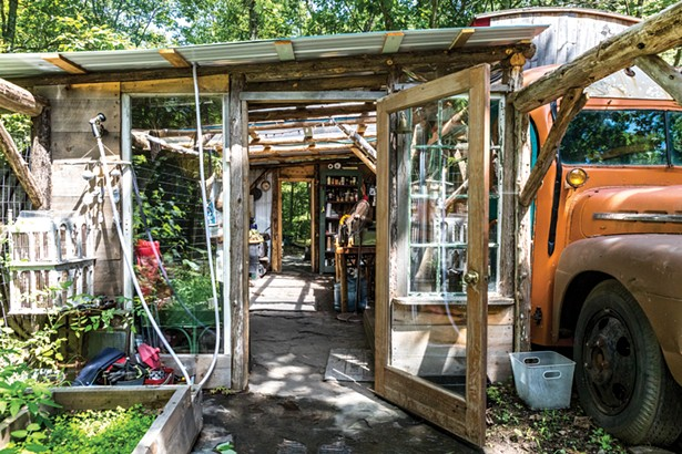 """Adjacent to Quick's bus, the couple built an outdoor kitchen with a clear plastic roof and a large fire pit nearby. They use both through the winter. """"We are trying to be as off-grid as possible,"""" he says. - PHOTO BY WINONA BARTON-BALLENTINE"""