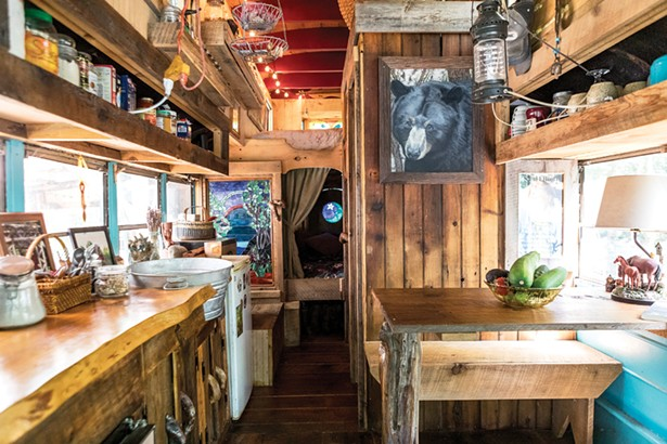 """Quick tore out the interior of his bus and rebuilt it from boards from a close friend's house and wood salvaged from a barn. """"I don't like taking down trees,"""" says Quick who mostly utilizes fallen logs or otherwise salvaged wood for his work. - PHOTO BY WINONA BARTON-BALLENTINE"""