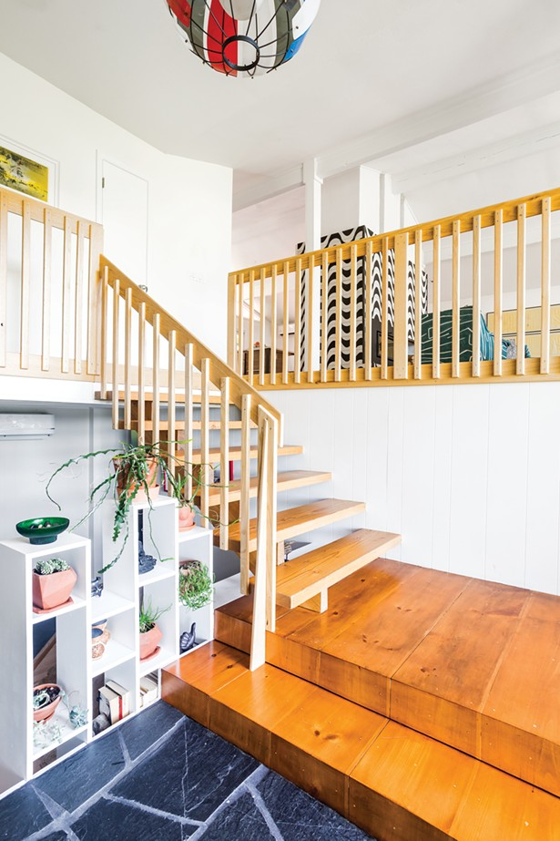 The couple completely remodeled the home's front entryway by sanding the floating staircase and adding new railings. At the lowest level, they replaced the railing with a built-in bookcase for both succulents and books. - PHOTO BY WINONA BARTON-BALLENTINE