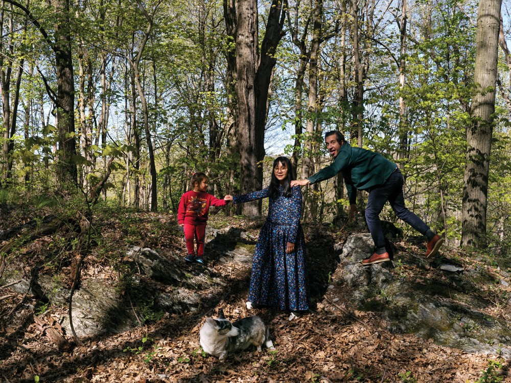 """Chris Mottalini, his wife Nepal Asatthawasi, and their son Nino on a stone outcropping near their house. The 1950 home was originally handbuilt from bluestone harvested from the surrounding land by an Irish stonemason. """"There are stone walls running all through the woods here,"""" says Mottalini. - PHOTO BY CHRIS MOTTALINI"""