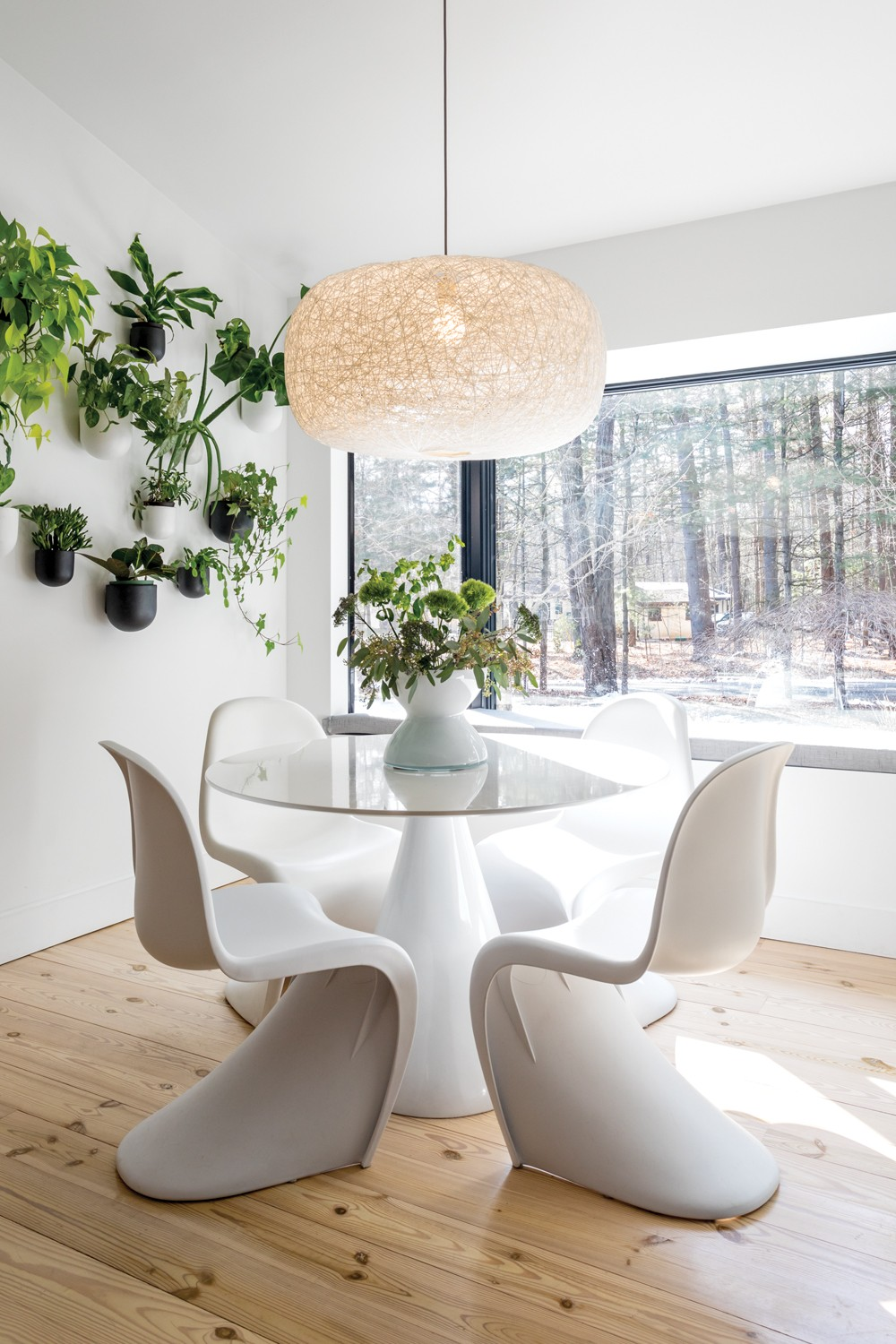 "Sun floods into Oldenburger and Smykowski's kitchen, - even on winter days. The thriving wall garden adds layers of - green to the beige-on-white design. Oldenburger found two - of the Vernor Panton chairs by Vitra at a vintage shop and - matched them with a round table and pillar pedestal base. - The wall pots and hanging lamp are both by West Elm. ""I do - love plants,"" she says. ""I try to have live plants throughout - the house and encourage my clients to also."" - PHOTO BY WINONA BARTON BALLENTINE"
