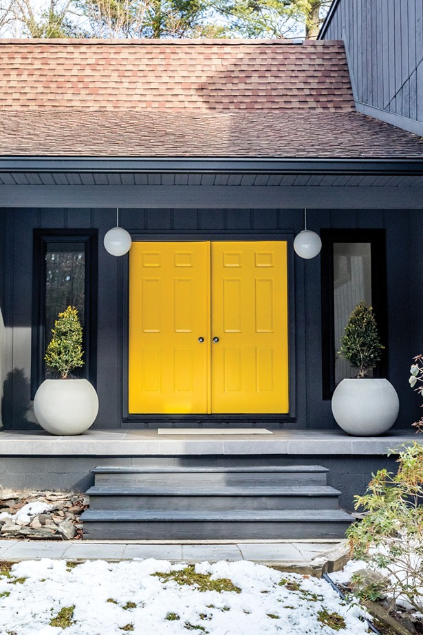 "Oldenburger painted the home's front double door entrance a striking yellow to contrast with the dark gray siding. White concrete planters match the vintage globe lights above. Oldenburger relied on contractor Tom Mayone for the majority of the home's seven-year renovation. ""We've worked together for the last 10 years on most of my projects,"" she says. ""And we've developed a vernacular and friendship that continues to make creating and renovating fun."" - PHOTO BY WINONA BARTON BALLENTINE"