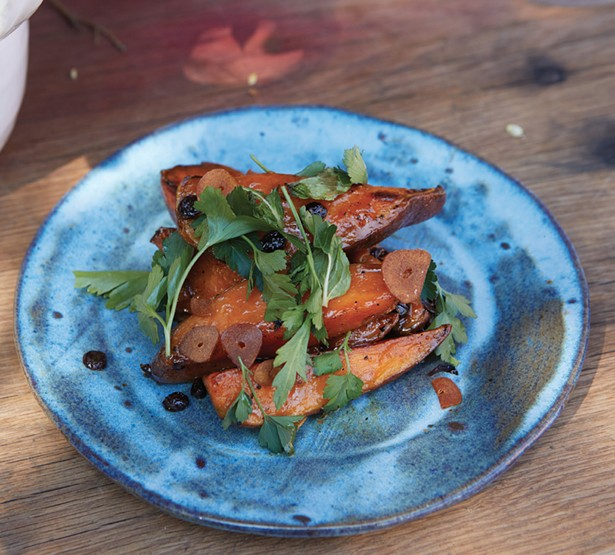Roasted sweet potatoes with anchovy vinaigrette, currants, and parsley.