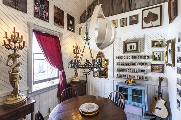 """The home's dining room is filled with Lalala's art and found treasures. By combining - photography, sketching, painting, sculpture, and found art, she's created a diverse body of intricate work """"comprised of spiritual, social, and psychological investigations."""" - WINONA BARTON-BALLENTINE"""