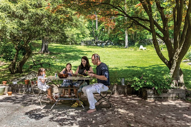 """Winick, Bloomberg, and their daughters enjoying a meal on their backyard patio. """"We also have a covered porch,"""" says Winick. """"It's our own outdoor living room and dining room and we use it as many days as the weather allows."""" - WINONA BARTON-BALLENTINE"""