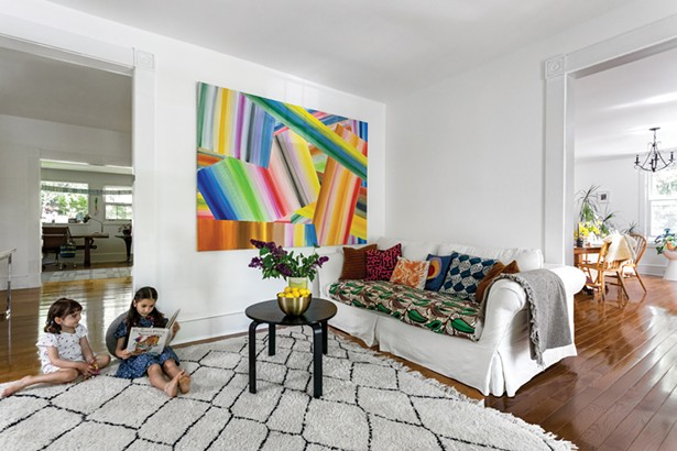 The children enjoying a calm moment in the home's living room. The abstract painting is by Sam Schonzeit. Winick re-covered the family's hand-me-down couch with Congolese textiles gifted from a friend, and decorated it with pillows from Hungary and Mexico and quilted pieces created by her mother-in-law. - WINONA BARTON-BALLENTINE