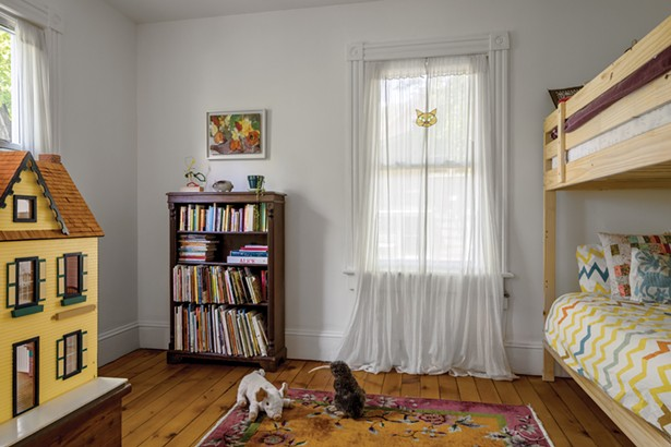 The second-floor children's bedroom showcases the home's pine plank flooring. Winick found a second-hand dollhouse for her daughters and hung a painting by their paternal great grandmother Edith Horton—a Viennese refugee and prolific painter who died last year at the age of 99. - WINONA BARTON-BALLENTINE