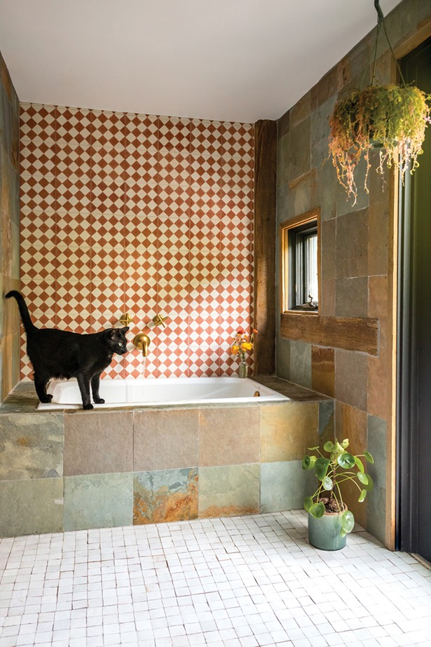 Downstairs, Hall converted a former second kitchen into a full guest bathroom. Influenced by a trip to Morocco, Hall wanted to capture the colors, textures, and lighting she'd found while traveling though the country. She found bronze and beige handcrafted ceramic tile for the bathtub wall and paired it with mother-of-pearl mosaic tile for the floors—all from Mosaic House in Manhattan. - WINONA BARTON-BALLENTINE