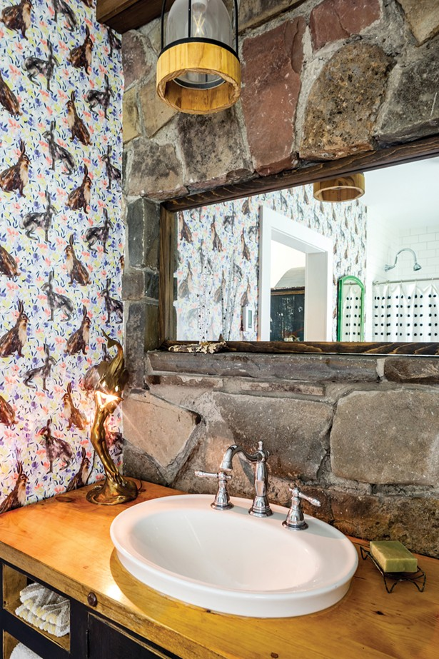 Facci and Gironda captured space from a closet to expand their en suite bathroom. After completely revamping the bathroom with a tiled shower, wooden vanity, and new mirror, they finished the space with whimsical wallpaper. - WINONA BARTON BALLENTINE