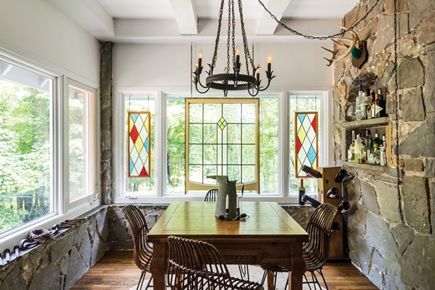 Gironda and Facci suspect their dining area was once an outdoor porch that was eventually enclosed. They left one of the bluestone walls exposed and accentuated the stone walls and trim by adding an iron chandelier. A cut-out in the stone wall serves as an ad hoc bar. - WINONA BARTON BALLENTINE