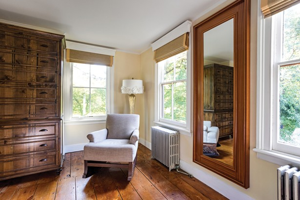 The house's second-floor bedrooms feature the original wide-plank wooden floors. Jackson designed and built the farmhouse country dresser from knotty pine and then stained it to match the room. - WINONA BARTON-BALLENTINE