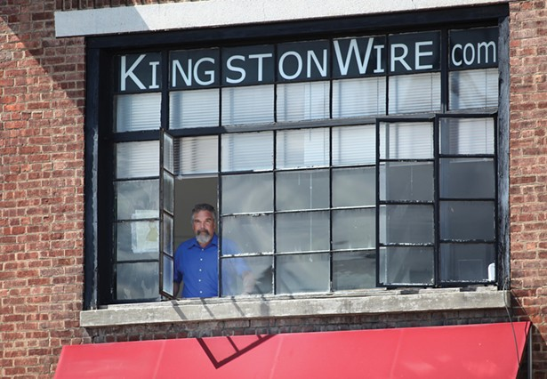 Reporter Jesse Smith in the Kingston Wire office overlooking the intersection of Broadway and Grand Street. Kingston Wire is a subscription-based digital newsroom covering the city that launched in 2020. - DAVID MCINTYRE