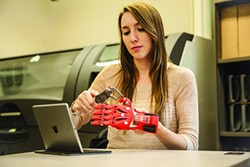 A New Paltz student working with a 3D printed robohand, designed and built at SUNY New Paltz's Hudson Valley Advanced Manufacturing Center. - SUNY NEW PALTZ