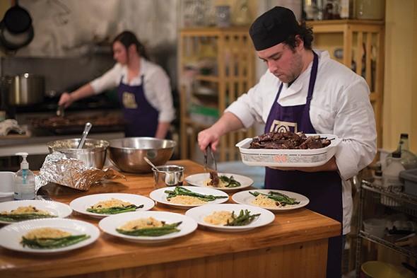 Chef Rob Handel and Farm Manager Amanda Hughes plating slow-roasted pomegranate molasses glazed lamb breast ribs - JIM MAXIMOWICZ