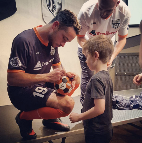 Player signs ball for a young supporter at the 2016 Kit Unveiling Party at the Senate Garage in Kingston - MICHAEL CIRCE