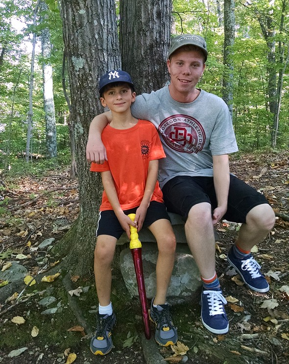 Sam Hollman, age 8, gives Johan Fridlund, age 18, a tour of the woods behind his house on Fridlund's first day with his American host family - JESSICA GREENSTEIN