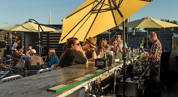 Derek Williams tending bar on the rooftop deck at Redwood - FRANCO VOGT