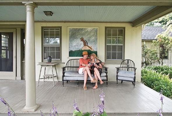Valerie Shaff and Stephen Kingsley enjoying their front porch. Behind them hangs a painting of a chipmunk by outsider artist Earl Swanigan. - DEBORAH DEGRAFFENREID
