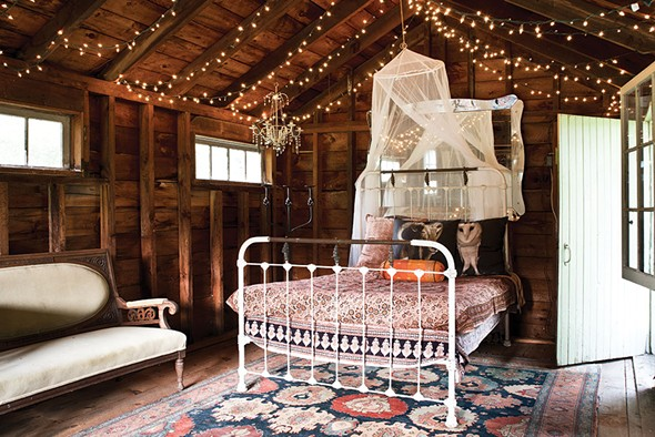 An iron bed in the outbuilding is decorated with Shaff's owl portraits printed on pillows. - DEBORAH DEGRAFFENREID
