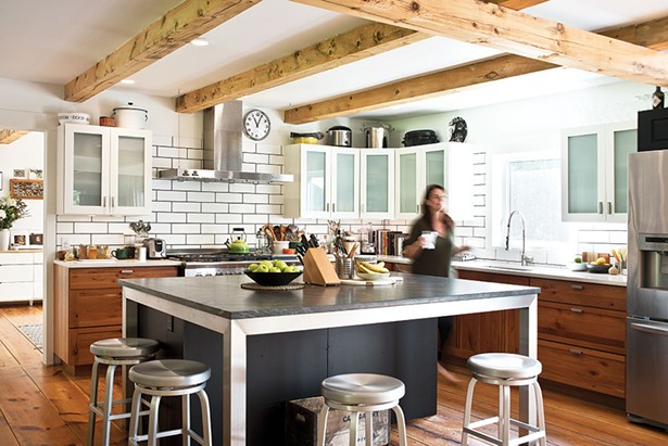 """The couple renovated the home's original kitchen.They hired local blacksmith Jonathan Nedbor to create a Parson's table frame expanding the original kitchen island. - Barra & Trumbore Stone Fabricators created the Jet Mist granite island top and white quartz counters. """"This is the most fun kitchen we've ever had,"""" explains Cummings.""""We've had 14 people in here cooking and still were able to move around comfortably."""" - DEBORAH DEGRAFFENREID"""