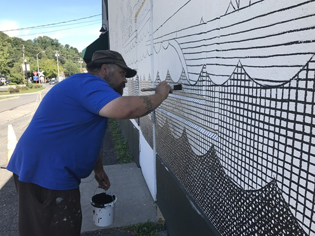 Matthew Pleva works on a mural at the Riverport Wooden Boat School for O+ Kingston. - KATHLEEN MURRAY