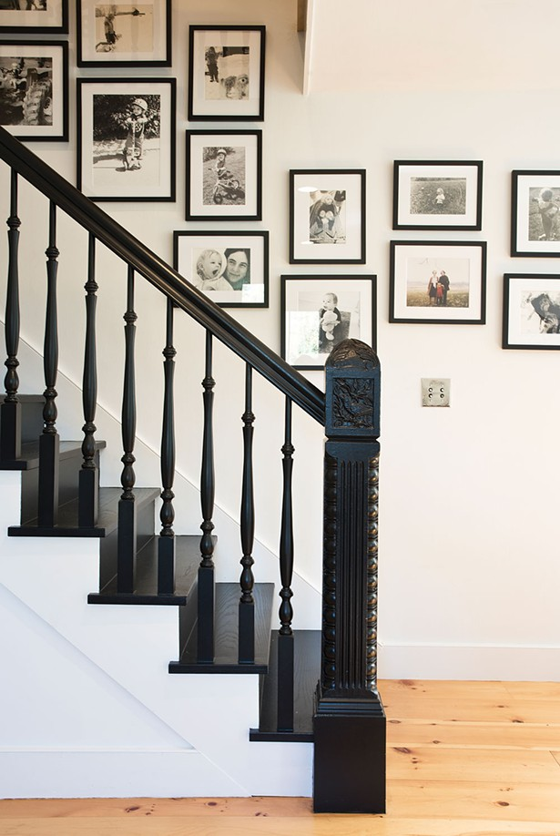 Von Stoddard expanded the home's original staircase and added an antique newel post from Zaborski's Emporium in Kingston. The team painted the entire staircase black. The wall behind displays two generations of black-and-white photos—memories of her own childhood intermixed with her son's first years. - DEBORAH DEGRAFFENREID