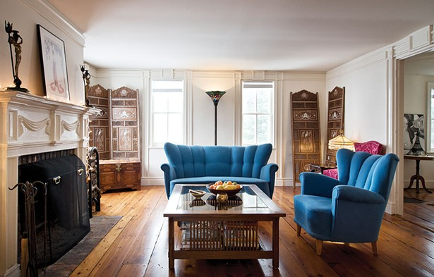 """The home's living room features an original working fireplace with an ornately carved mantle. The room's paneled walls and detailed crown molding add further appeal. """"The house has a lot of charm but no level surfaces,"""" says Thompson. - DEBORAH DEGRAFFENREID"""
