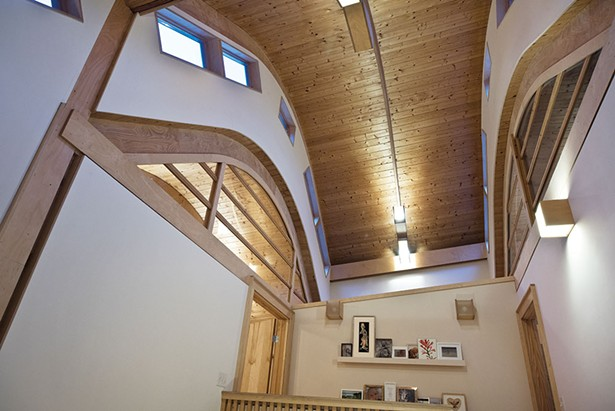 The home's barrel-vaulted ceiling and multiple interior and exterior windows enhance the bright, boundless space. A mix of the couple's own artwork, friends' pieces, and family photos line the walls. - DEBORAH DEGRAFFENREID