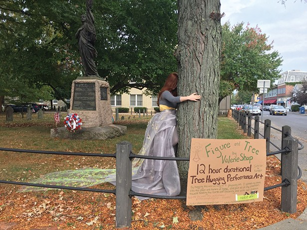 Figure and Tree: a photo by Kathleen Murray of a duration performance art piece by Valerie Sharp in which Sharp embraced a tree in the Old Dutch Church graveyard from sunrise to sunset during the 2017 O+ festival in Kingston.