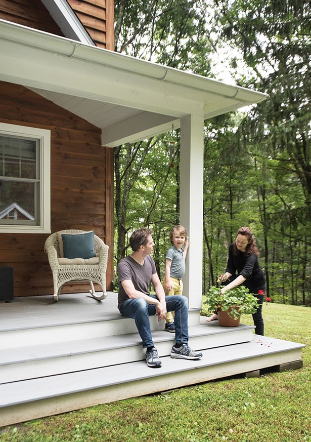 "Bollman and Nicholas with their son Hudson on the front veranda. The home's construction ""was a collaboration—my wife and I drove the whole process,"" says Bollman. However, their new neighbors stepped in and helped with everything from the tear down to the milling to the framing and construction. - DEBORAH DEGRAFFENREID"