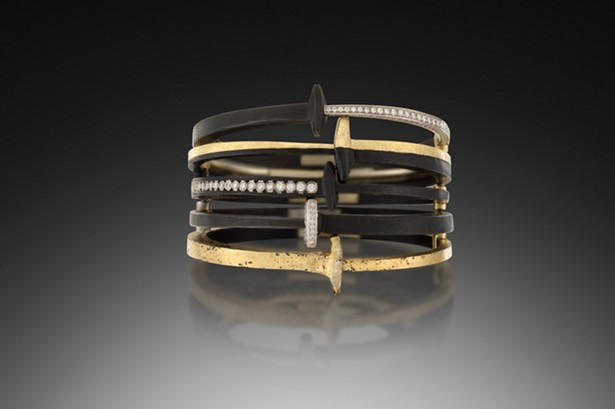 A stack of Pat Flynn's iconic nail bracelets, made with blackened steel, 22k gold, and diamonds.