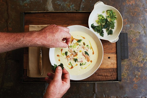 Binnekill Tavern chef Bryan Calvert plating smoked trout soup with crispy parsley. - NATALIE CHITWOOD