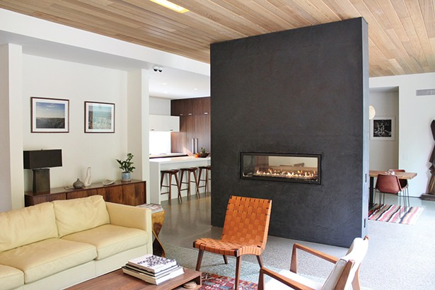 A see-through fireplace serves as a divider between the dining and living areas.