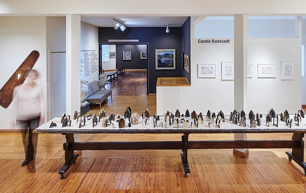 Pressing On installation, 86 antique sad irons on 16' wooden table by Elizabeth M. Fraser (ca. 1920), Woodstock Artists Association & Museum - PHOTO BY KEVIN KUNSTADT
