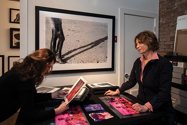 """In Rice's studio, she and neighbor Amy Pilkington look over Rice's pictures of Studio 54's opening night. A fellow artist, Pilkington also modeled for the print hanging along the back wall entitled """"Woman in Chaps"""" Bridgehampton, NY. - PHOTO: DEBORAH DEGRAFFENREID"""