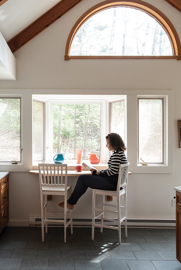 """Alison Stewart in the sunny kitchen of her Woodstock retreat overlooking the woods. As of late, the home's solitude has lent itself well to reading the authors she hosts on her WNYC program """"All of It."""" """"It's a dream job,"""" she explains, """"especially for a working mom who was an English major. In the past six months, we've had 570 guests."""" She adds, """"I really think if someone has spent all that time working on a book, I should offer them the - courtesy of trying my best to read it."""" - PHOTO: DEBORAH DEGRAFFENREID"""