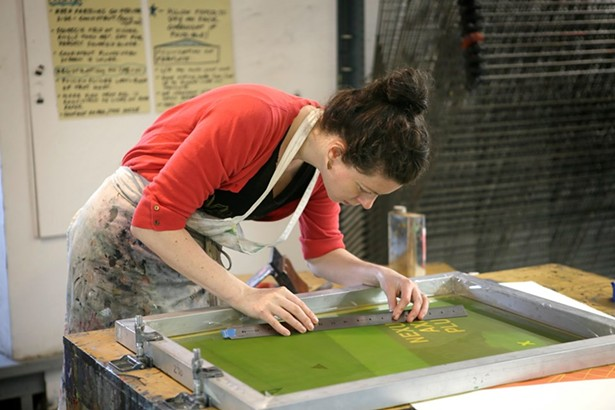 Studio Workspace Resident Sarah McDermott setting up a silkscreen project at the omen's Studio Workshop.